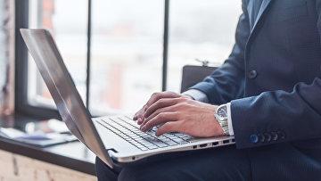 Бизнесмен работает за компьютером. Архивное фото