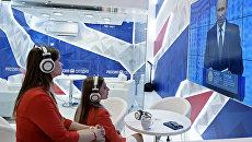 Участники смотрят трансляцию выступления президента России Владимира Путина на Петербургском экономическом форуме