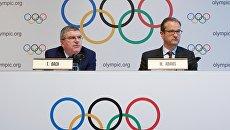 Президент МОК Томас Бах и директор по коммуникациям Марк Адамс на пресс-конференции по итогам специального заседания Международного олимпийского комитета в Лозанне