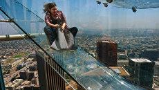 Женщина скользит вниз по Skyslide на внешней стороне Bank Tower в Лос-Анджелесе, США. Июнь 2016
