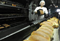 Работница вынимает из формы готовый хлеб