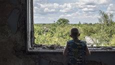 Подросток у окна в разрушенном спортивном зале средней школы поселка Шахты 6/7 близ Горловки. Архивное фото