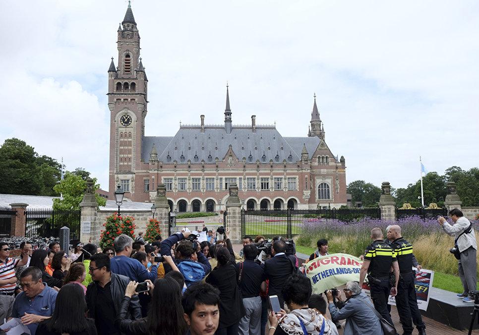 Демонстранты, полицейские и журналисты у здания Постоянной палаты третейского суда в Гааге. 12 июля 2016