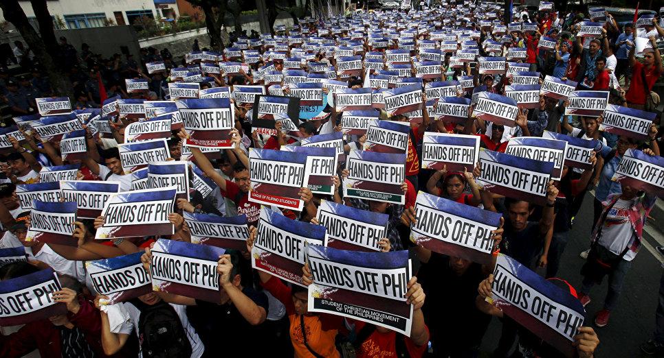 Активисты держать плакаты с надписью Руки прочь от Филлипин! во время акции протеста по спорам в Южно-Китайском море