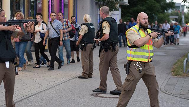 La polizia accompagnati da persone che lasciano la costruzione del centro commerciale, dove l'ignoto ha aperto il fuoco