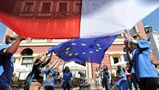 Молодые люди держат флаги Польши и Евросоюза во время демонстрации в Варшаве, Польша. Архивное фото