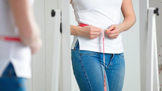 Девушка измеряет объем талии. архивное фото