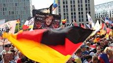 Участники акции протеста в Берлине против политики Ангелы Меркель