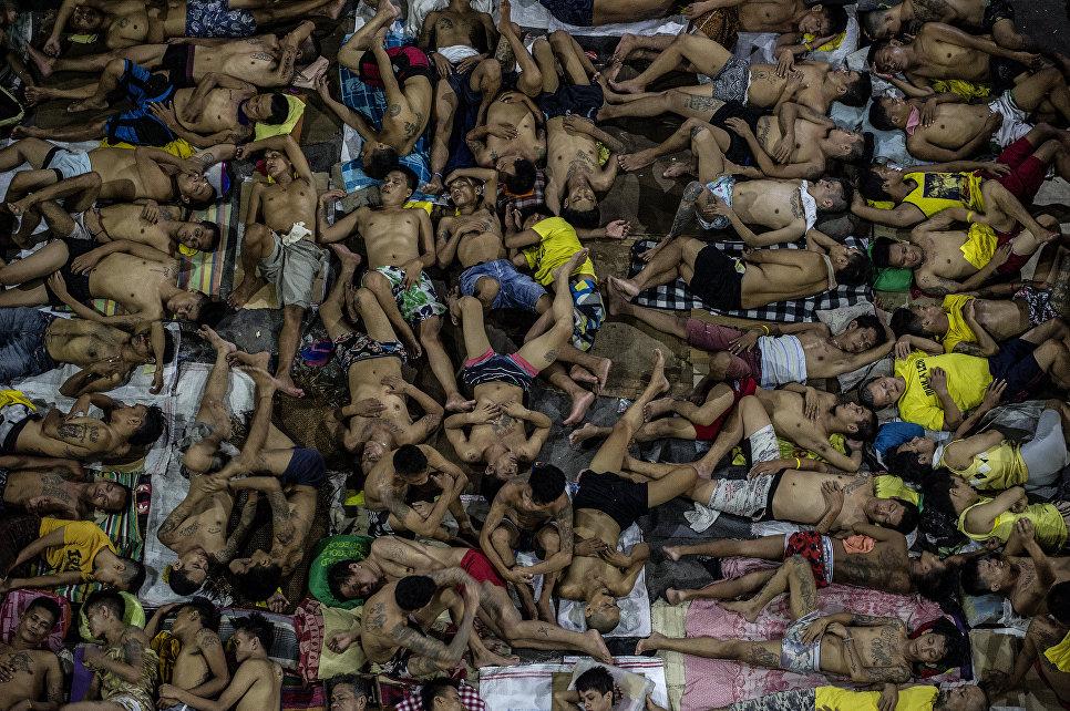 Заключенные спят на земле, на открытой баскетбольной площадке в филиппинской тюрьме.