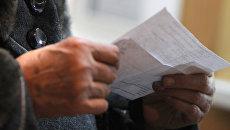 Женщина проверяет правильность заполнения квитанций. Архивное фото