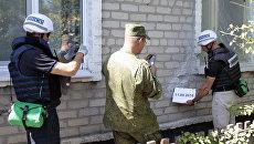 Представители ОБСЕ осматривают повреждения, нанесенные жилому дому в результате обстрела поселка Крутая балка. Архивное фото