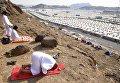 Паломники совершают молитву на горе у палаточного лагеря в Мине