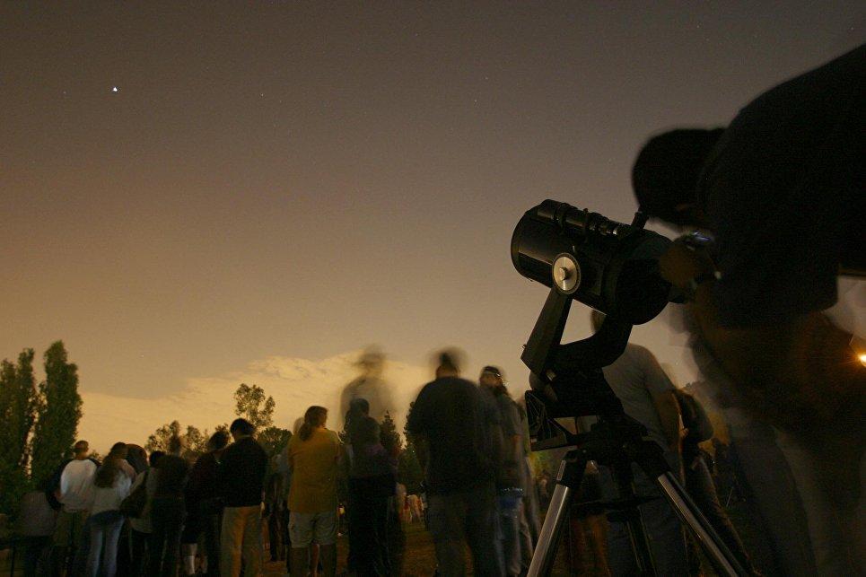 Люди смотрят через телескоп на Марс в Лос-Анджелесе