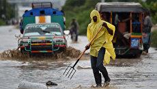 Местный житель убирает мусор с затопленной улицы на Гаити