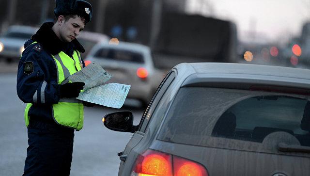 Сотрудник дорожно-патрульной службы ГИБДД проверяет документы у водителя автомобиля