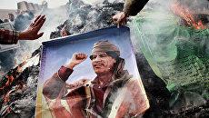 Житель Бенгази сжигает портрет Муамара Каддафи. Архивное фото
