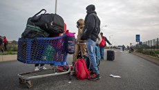 Беженцы в специально организованном центре по распределению мигрантов CAO рядом с лагерем Кале во Франции