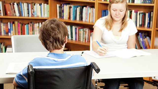 Ребенок с ограниченными возможностями в школьной библиотеке. Архив