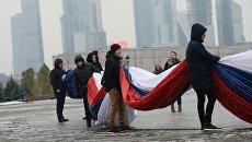 Участники церемонии демонстрации самого большого флага Российской Федерации в парке Победы в Москве