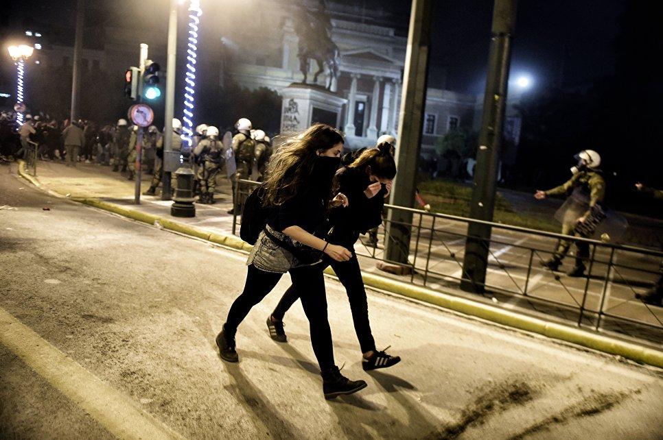 Прохожие во время массовой демонстрации против визита президента США Барака Обамы в Афины