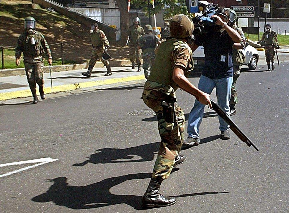 Телеоператор снимает разгон демонстрантов в Каракасе, Венесуэла