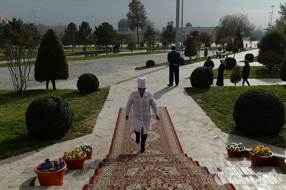 Женщина подходит к избирательному участку во время выборов президента Узбекистана