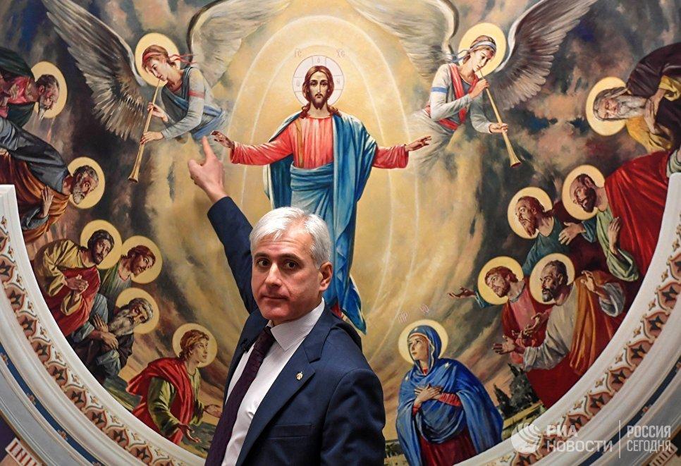 Художник Василий Нестеренко на фоне своей работы на открытии выставки Русский Афон