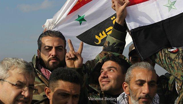 Солдаты сирийской армии фотографируются с флагом на крыше освобожденного района Алеппо. Архивное фото