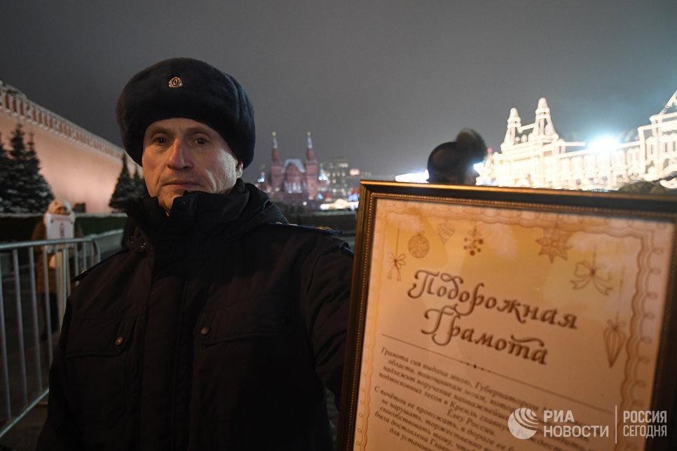 Сотрудник правоохранительных органов демонстрирует подорожную грамоту для проезда специального автопоезда с главной Новогодней елкой России на территорию московского Кремля