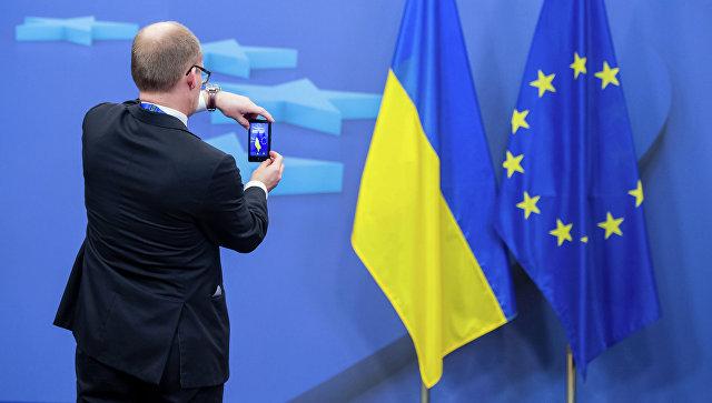 Человек фотографирует флаги Украины и Евросоюза. Архивное фото