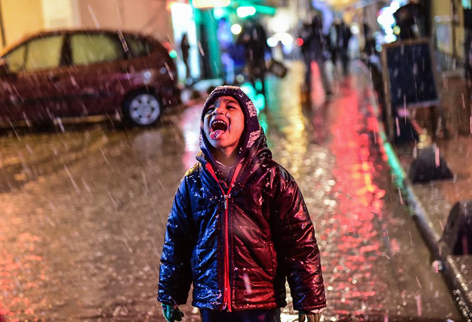 Мальчик радуется снегу в Стамбуле, Турция