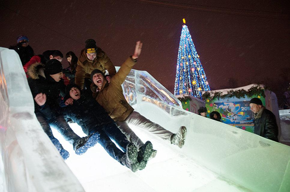 Местные жители катаются с горки во время встречи Нового 2017 года на центральной площади в Томске