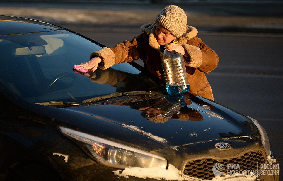 Женщина чистит от инея лобовое стекло машины в морозный день в Москве