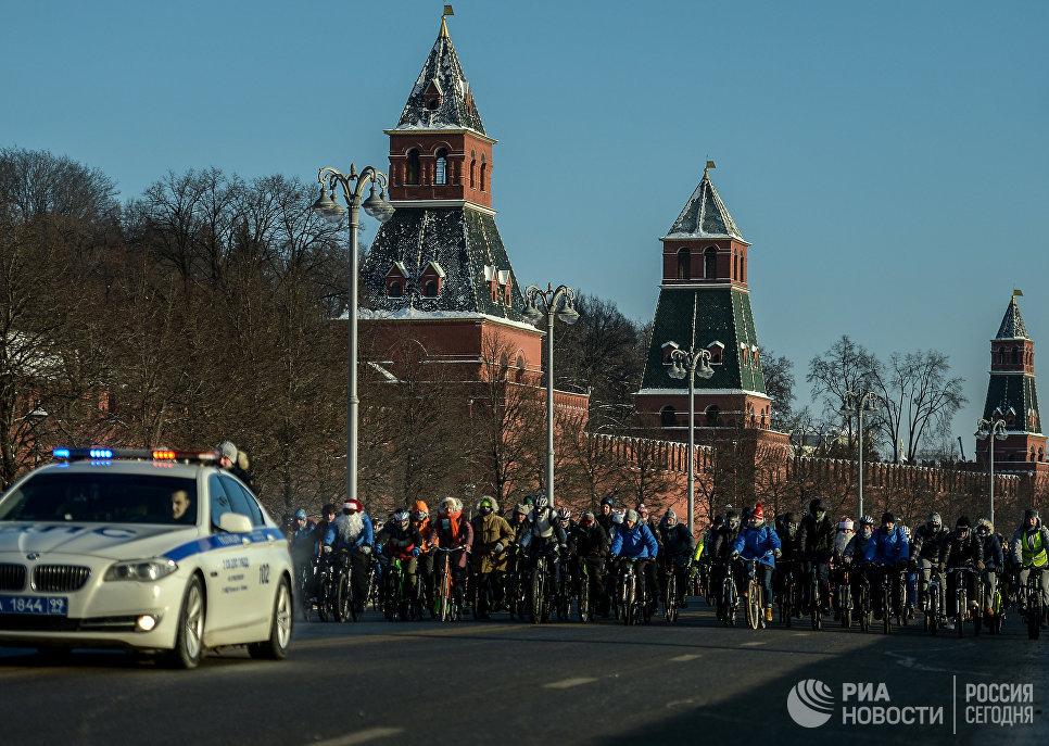 Участники Второго зимнего Московского Велопарада в сопровождении машины сотрудников ДПС на Кремелвской набережой