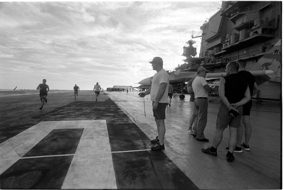Личный состав тяжелого авианосца Адмирал Кузнецов в промежутках между боевыми заданиями проводит сдачу 100 метровой дистанции на палубе крейсера. Средиземное море,  14.10.2016