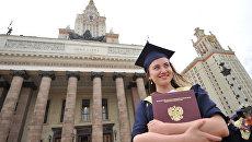Выпускница университета после церемонии вручения дипломов у Главного здания МГУ имени М.В.Ломоносова. Архивное фото