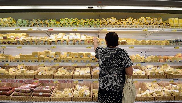 Женщина у прилавка с сырами в гипермаркете. Архивное фото