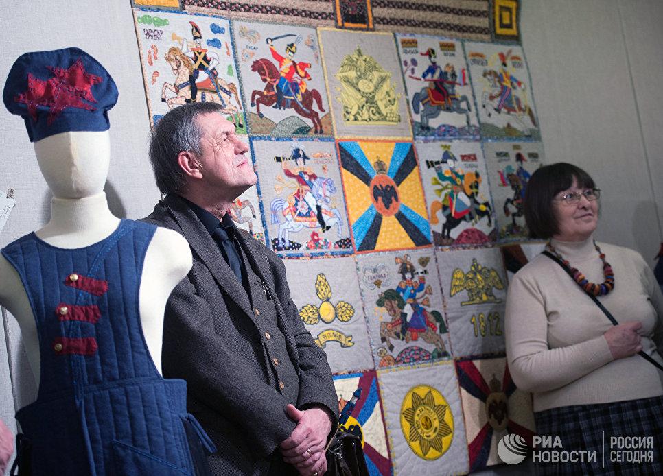 Посетители у коллективной работы 1812 год - работы участников студии лоскутного шитья Красный сарафан на открывшейся выставке Аты-баты