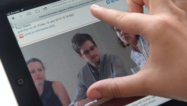 Журналист смотрит на экран компьютера, на котором открыта фотография экс-сотрудника ЦРУ Эдварда Сноудена.
