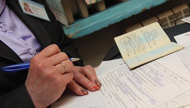 Сотрудница паспортной службы помогает в оформлении документов для получения российского паспорта. Архивное фото