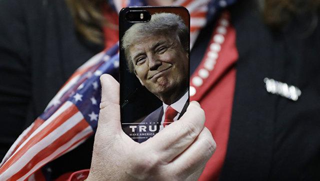 Женщина держит телефон с фотографией Дональда Трампа во время предвыборной кампании в США