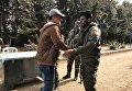 Боец сирийской армии жмет руку боевику из вооруженной оппозиции после досмотра на КПП города Сергая