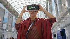 Девушка в 3D очках у стенда телеканала RT на Российском инвестиционном форуме в Сочи