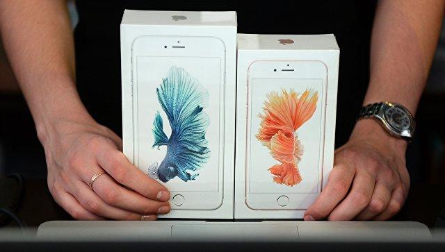 Продавец демонстрирует новые смартфоны Apple iPhone 6 и iPhone 6 plus. Архивное