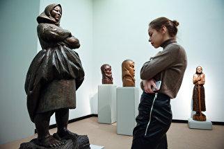 Девушка у скульптуры В.И. Мухиной Крестьянка на выставке Мужики и бабы в Третьяковской галерее на Крымском Валу в Москве