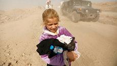 Иракская девочка бежит из своего дома в Мосуле