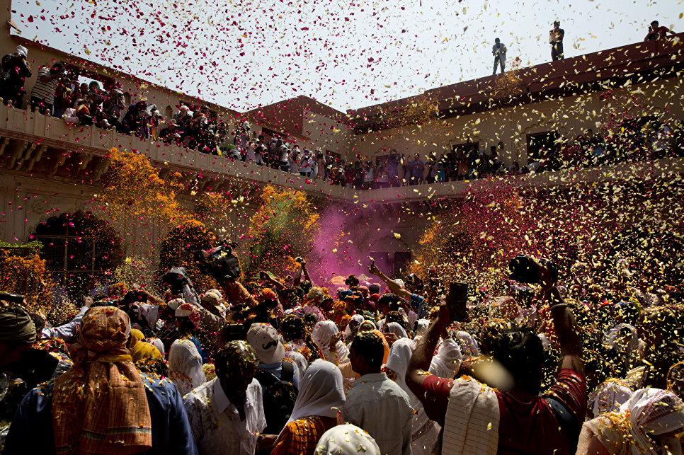 Местные жители и овдовевшие женщины принимают участие в фестивале Холи в храме Гопинатхи во Вриндаване, Индия