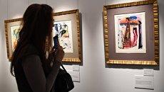 Посетительница знакомится с экспозицией на открытии выставки Сальвадора Дали Алиса в стране Чудес в галерее Altmans Gallery в Москве