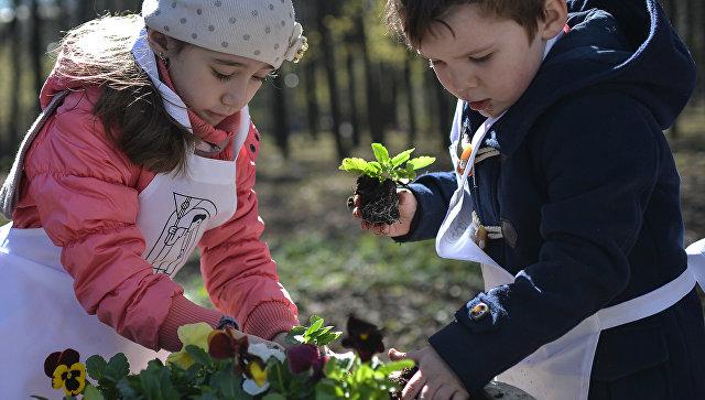 Дети высаживают цветы в клумбы в Нескучном Саду во время общегородского субботника