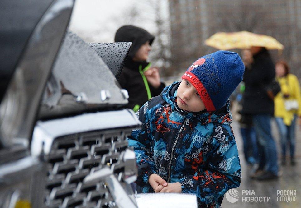 Мальчик рассматривает автомобиль ГАЗ 13 Чайка перед стартом автопробега 108 минут в Москве, приуроченного к 56-й годовщине полета человека в космос